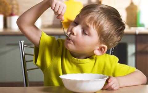 Criança comendo sozinha