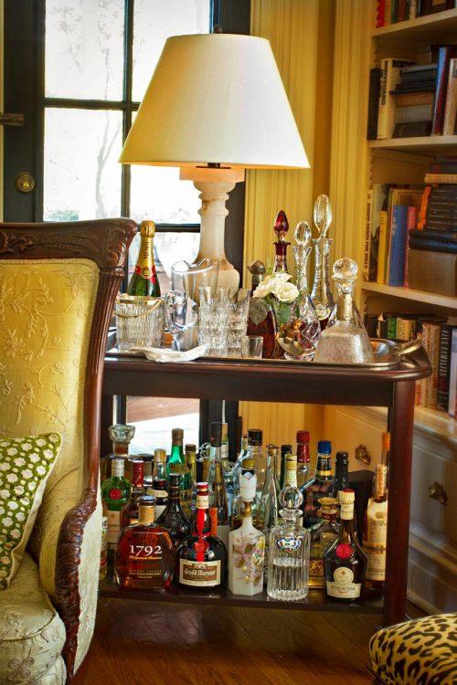 Bebidas e utensílios de bar dispostos na mesa lateral.