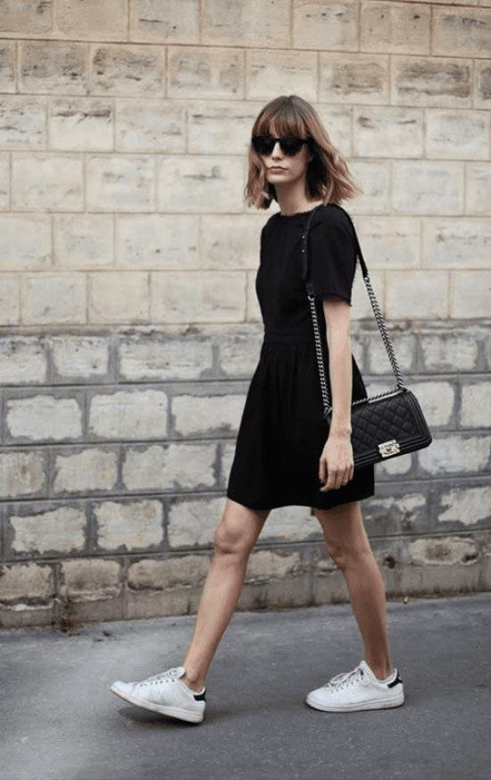Vestido preto com tênis branco.