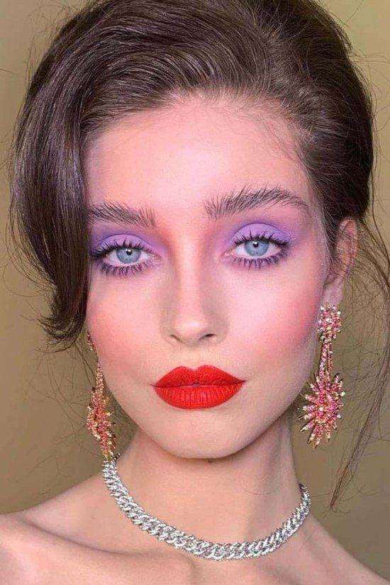 Maquiagem com sombra lilás e batom vermelho.