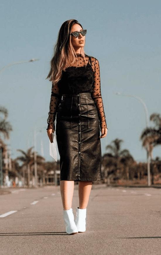 Look de blusa preta transparente com saia de couro.