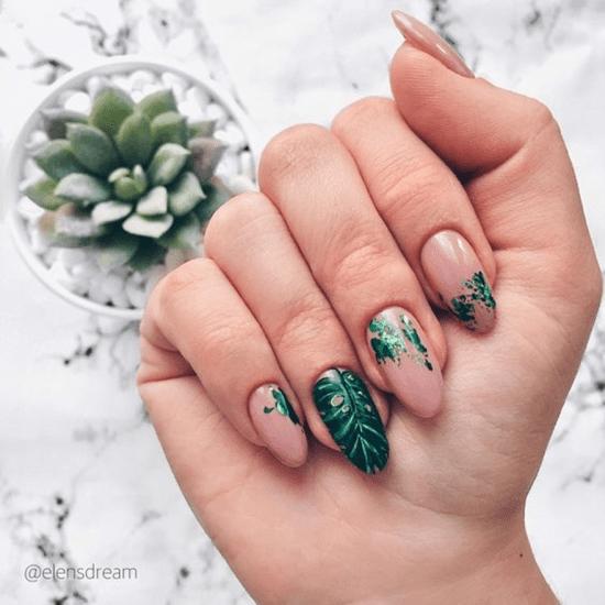 Unhas pintadas com motivos de folhas.
