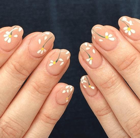 Unhas pintadas com flores.